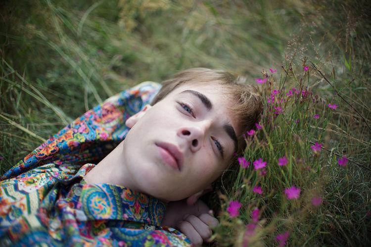 Portrait of man lying on grass