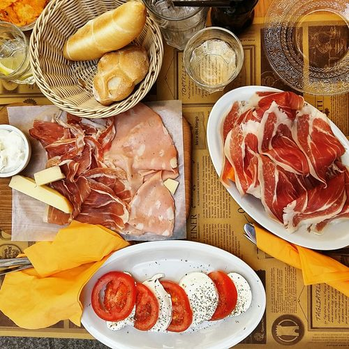 Directly above shot of meat with salad and breads on table