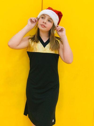 Cute girl wearing santa hat standing against yellow wall
