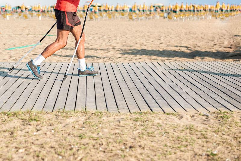 Low section of man walking on boardwalk