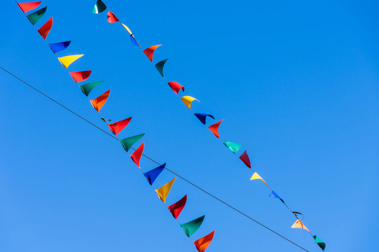 #urbanana: The Urban Playground Art And Craft Blue Blue Sky Bunting Celebration Clear Sky Copy Space Creativity Day Decoration Flags Flags In The Wind  Hanging In A Row Large Group Of Objects Low Angle View Multi Colored Nature No People Outdoors Shape Sky Streamer Triangle Shape Wind #urbanana: The Urban Playground Summer In The City Moments Of Happiness