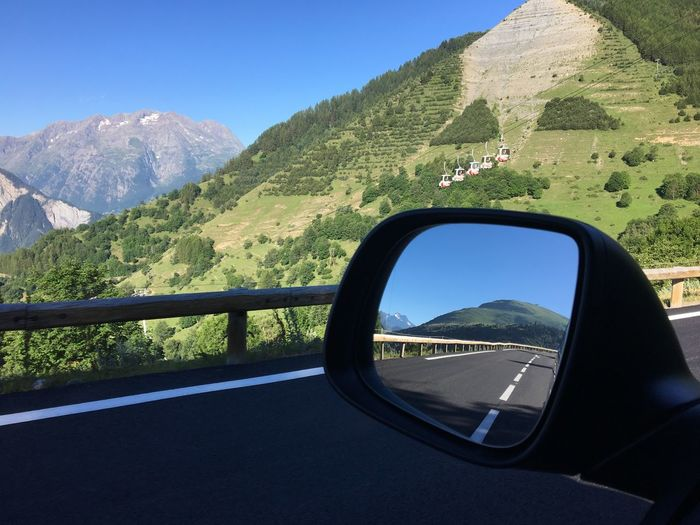 Reflection Of Road In Side-View Mirror Of Car Against Mountain
