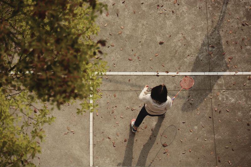 High Angle View Of Girl Playing Badminton