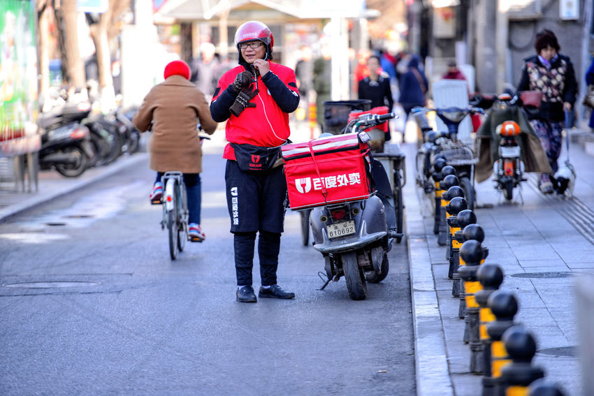 BEIJING, CHINA - MARCH 10, 2016: Food delivery courier with scooters brought orders to customers. ASIA Beijing Cars Cityscape Delivery Peking  Scooter Service Tourists Traffic Travel Capital China City Life Culture Destination Hutong Hutong Life Hutong Street Land Vehicle Mode Of Transportation Street Transportation Urban