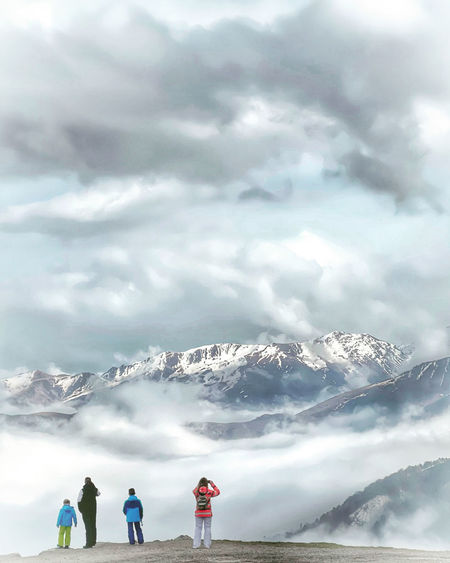 Rear view of people standing on snowcapped mountain against sky