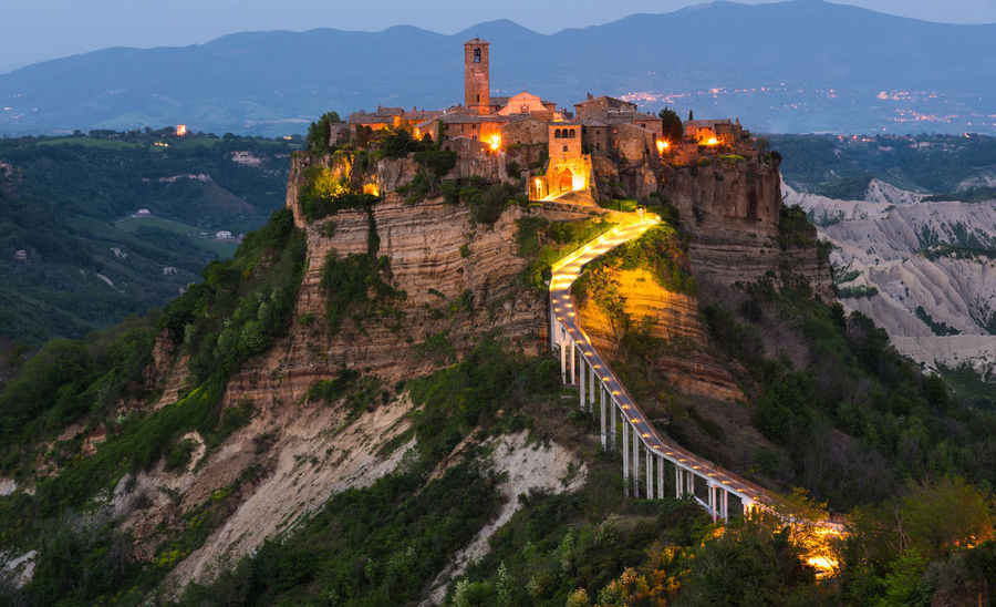 Bagnoregio, Italy Abbey Ancient Ancient Civilization Architecture Beauty In Nature Building Building Exterior Built Structure Castle Dusk Fort History Illuminated Mountain Mountain Range Nature No People Outdoors Scenics - Nature The Past Tourism Travel Travel Destinations