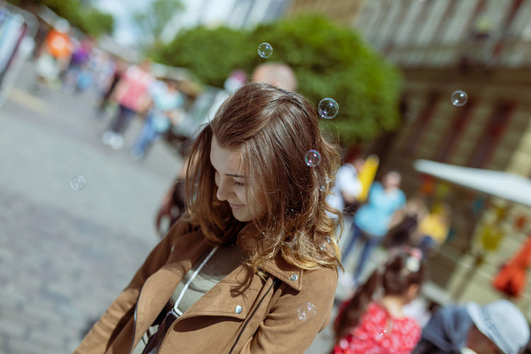 Young woman wearing overcoat while standing with bubbles on street