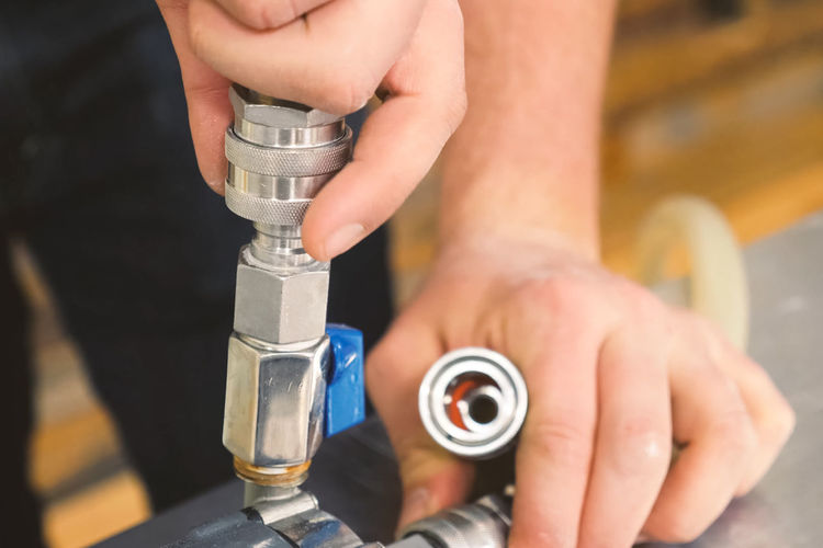 Cropped image of plumber attaching pipe on metal