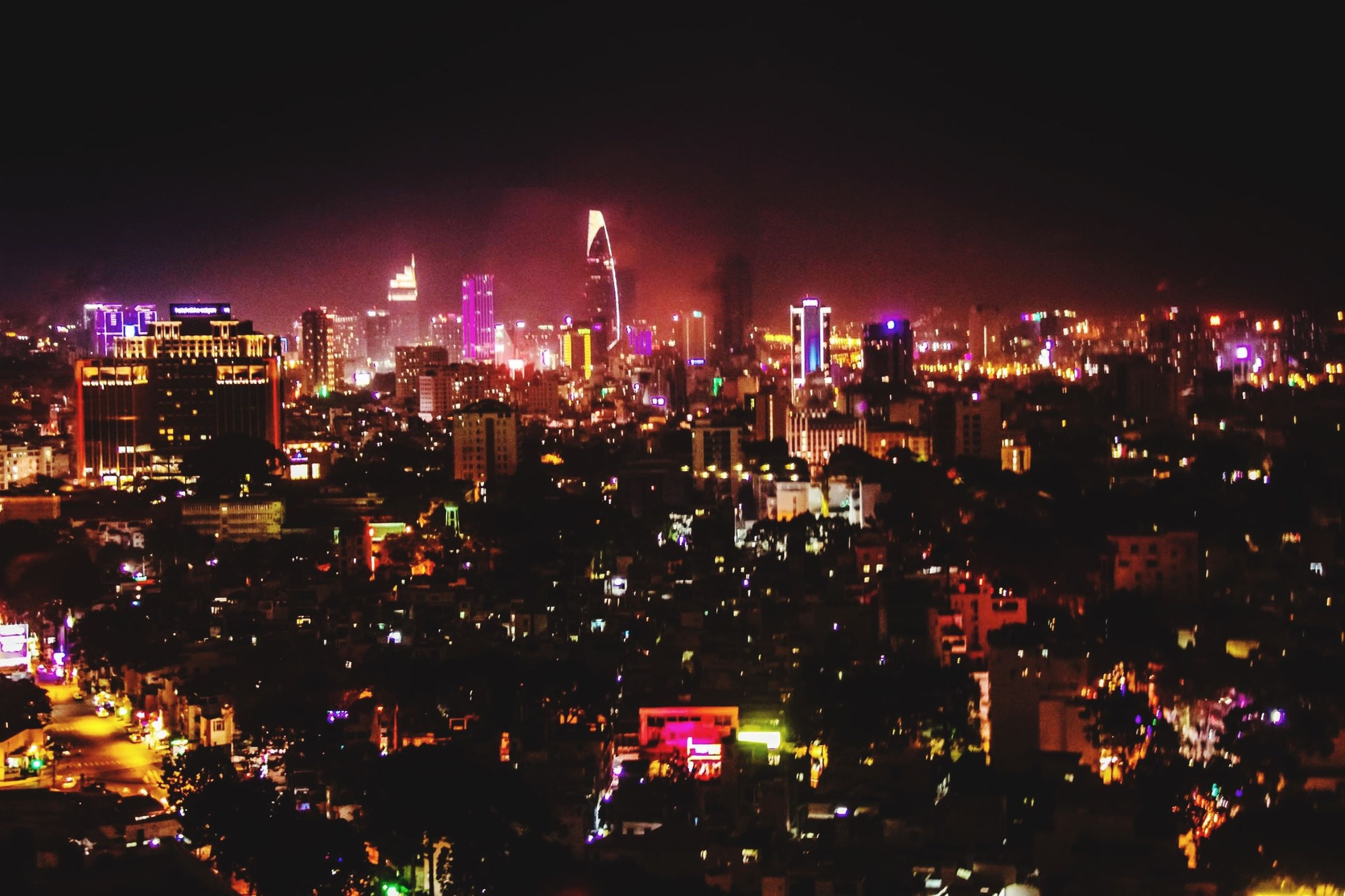 illuminated, night, city, building exterior, cityscape, architecture, skyscraper, built structure, crowded, tall - high, tower, high angle view, office building, city life, modern, urban skyline, capital cities, financial district, sky, clear sky