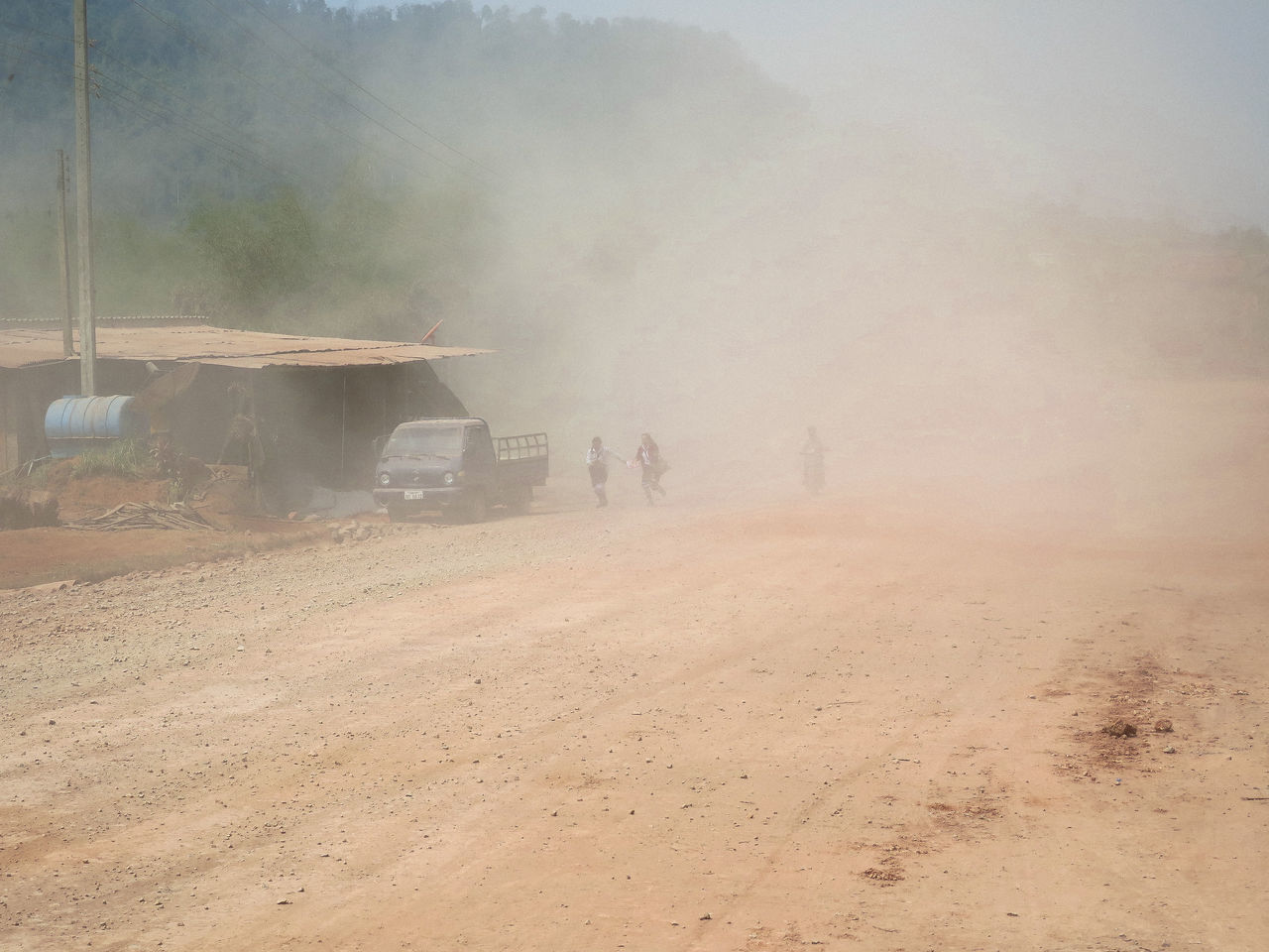 People Running In Dust Over Dirt Road