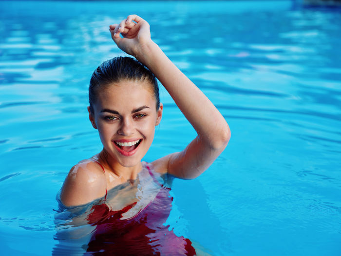 Portrait of smiling young woman swimming in pool