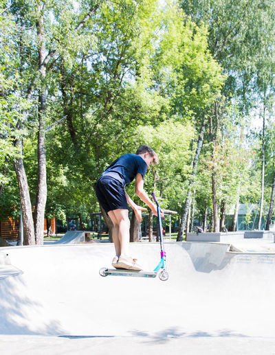 boy riding a scooter in a skatepark Full Length One Person Tree Plant Real People Leisure Activity Day Casual Clothing Sport Lifestyles Skateboard Men Balance Nature Young Men Child Sports Equipment Young Adult Skill  Outdoors Shorts