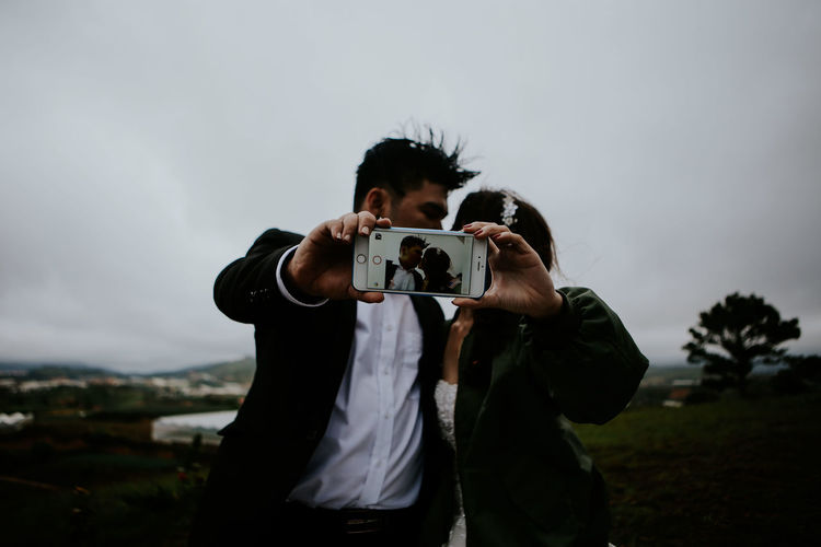 Camera - Photographic Equipment Digital Camera Digital Single-lens Reflex Camera Holding Home Video Camera One Person Outdoors People Photographer Photographing Photography Themes Sky Technology Wedding Photography