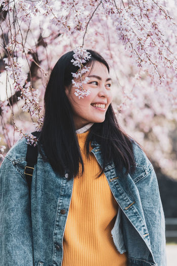 Portrait of smiling young woman standing by cherry tree