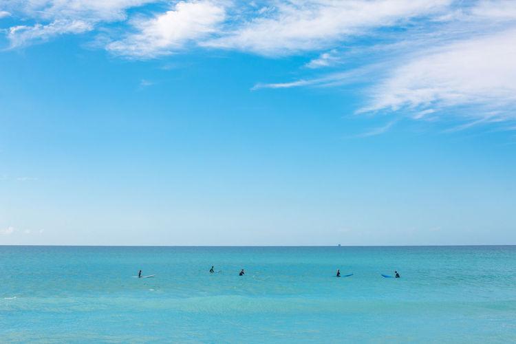 People surfboarding in sea