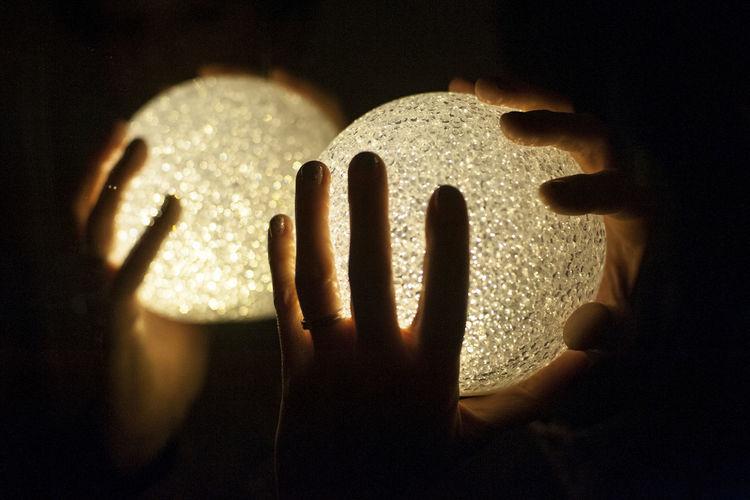 Close-up of human hands holding illuminated balls in darkroom