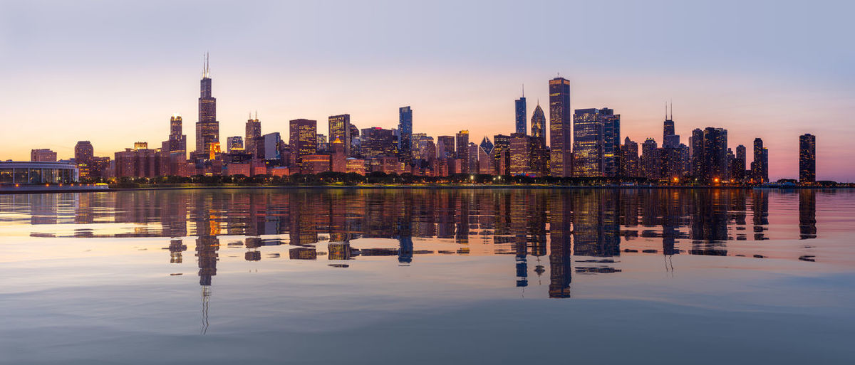 Wide panoramic shot of city skyline of Chicago reflected in an artificial water surface at sunset Chicago Cityscape Illinois Skyline Building Building Exterior City Cityscape Dusk Financial District  Golden Hour Illuminated Lake Landscape Modern Reflection Skyscraper Sunset Urban Skyline Water Waterfront Widescreen