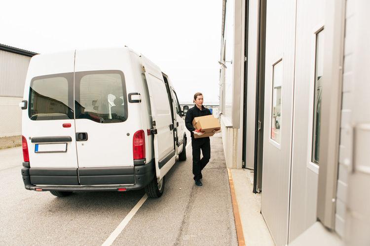 Rear view of man standing on car door