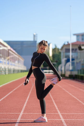 Fit woman stretching making functional training doing exercises for legs before jogging outdoors