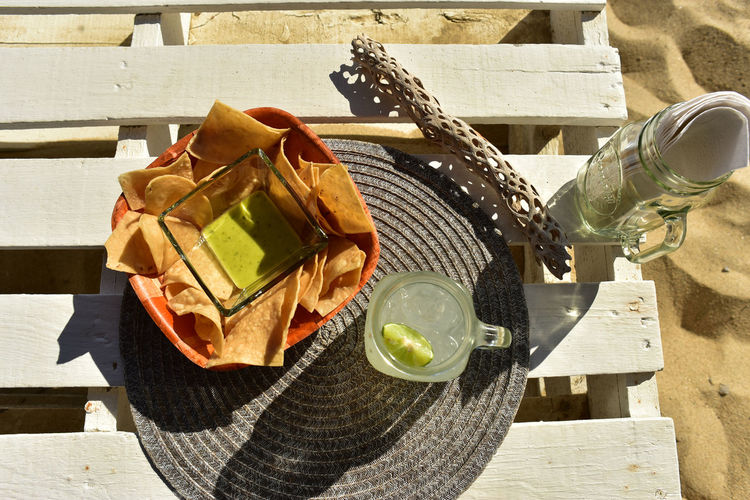 Snack of green salsa, tortilla chips and lemonade on table at beach in baja california sur, mexico