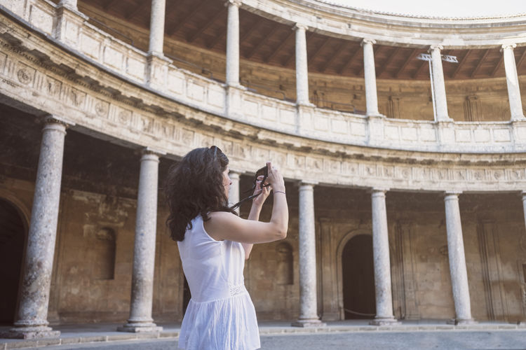 Woman photographing historical building