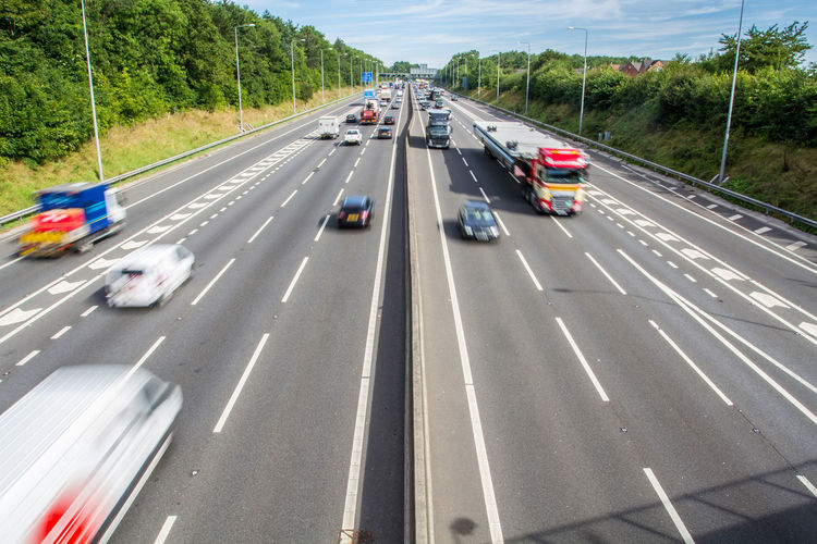 An aerial view of a busy motorway with speeding traffic in the UK Motorway Highway Freeway Autobahn Aerial View Traffic Busy Vehicle Speed Speeding Fast Motion Motion Blur Road Carriageway Lanes Cars Transport Transportation Logistics Getting There Uk Agency Street Link