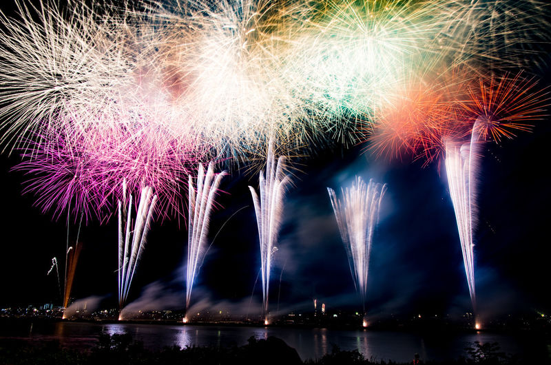 Low angle view of illuminated fireworks against sky at night