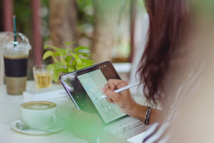 Midsection of design professional using digital tablet on table