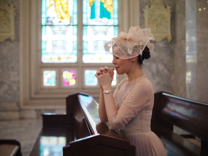 Side view of bride sitting in pew