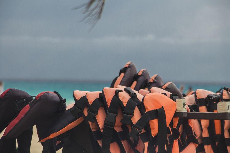 Close-up of life jackets hanging at beach