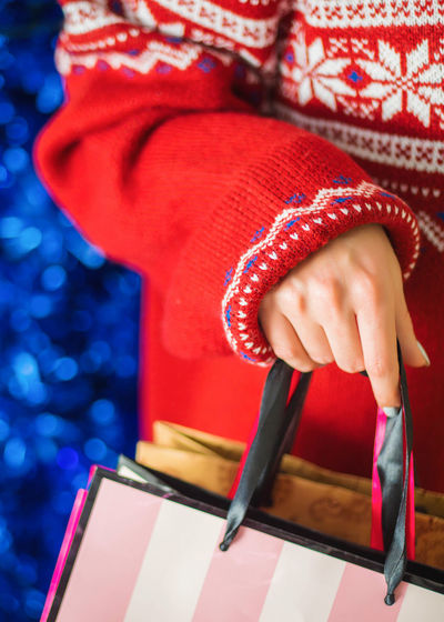 Midsection of woman holding bag during christmas