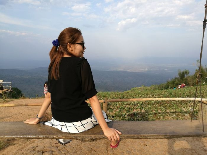 Rear view of woman sitting on wooden swing at mountain against sky