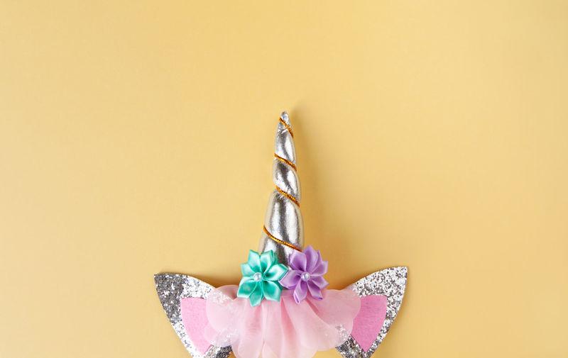 Close-up of unicorn horn on beige background