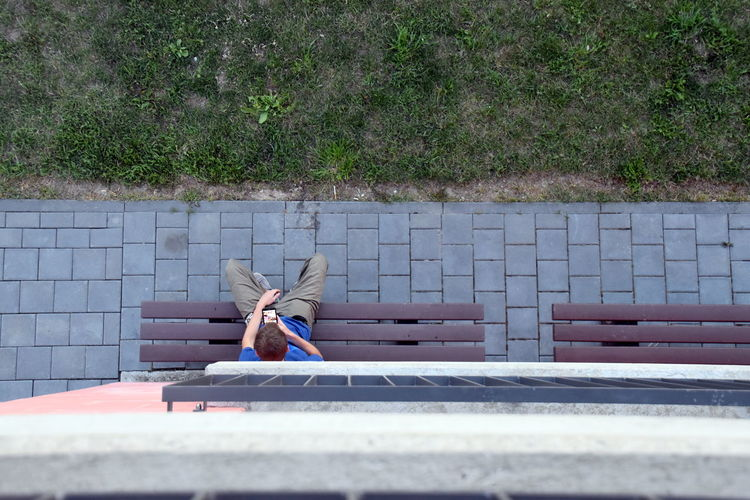 Boy sitting on bench with mobile phone, directly above