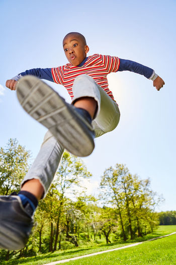 Low angle view of boy jumping against trees
