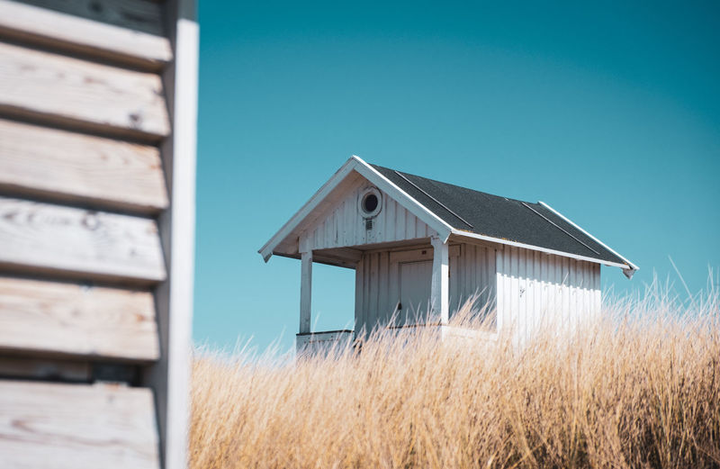 Wooden house on field against clear blue sky
