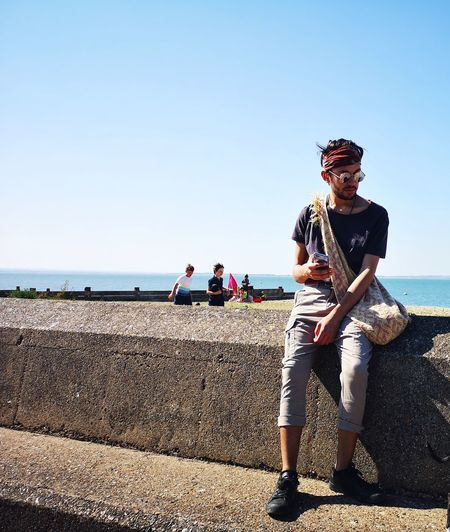 Full Length Of Young Man Sitting By Sea On Retaining Wall During Sunny Day