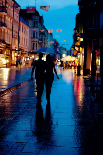 Rear view of woman walking on wet street at night