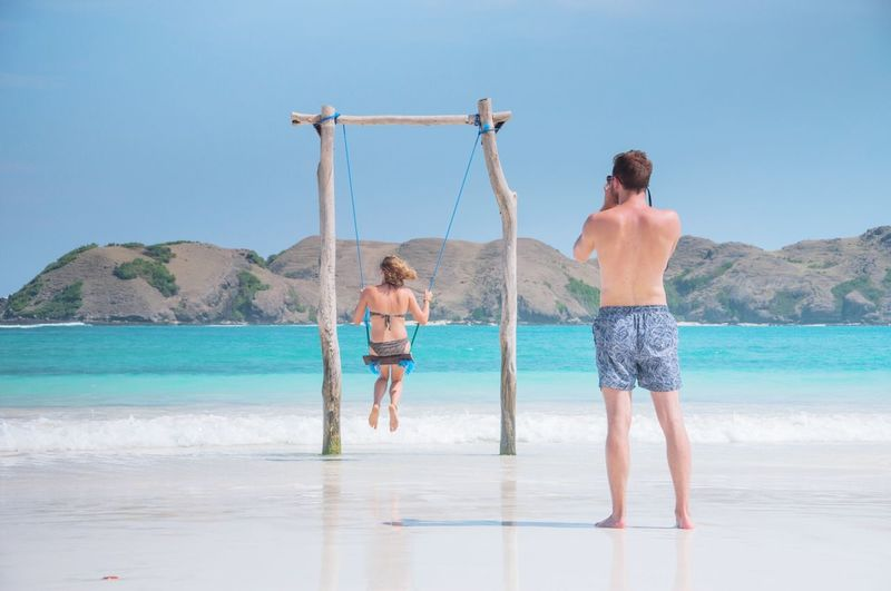 Man photographing woman on swing