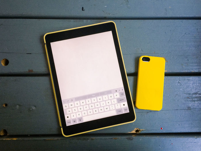 Tablet computer and mobile smart phone with yellow cases laying side by side on rustic blue table. Blank Blue Color Close-up Communication Computer Connection Control Copy Space Day Devices Information Mobile Morning No People Phone Smart Phone Smartphone Tablet Text Work Working Yellow