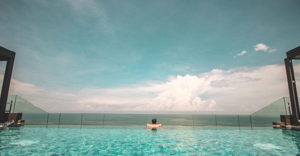Rear view of shirtless man in infinity pool