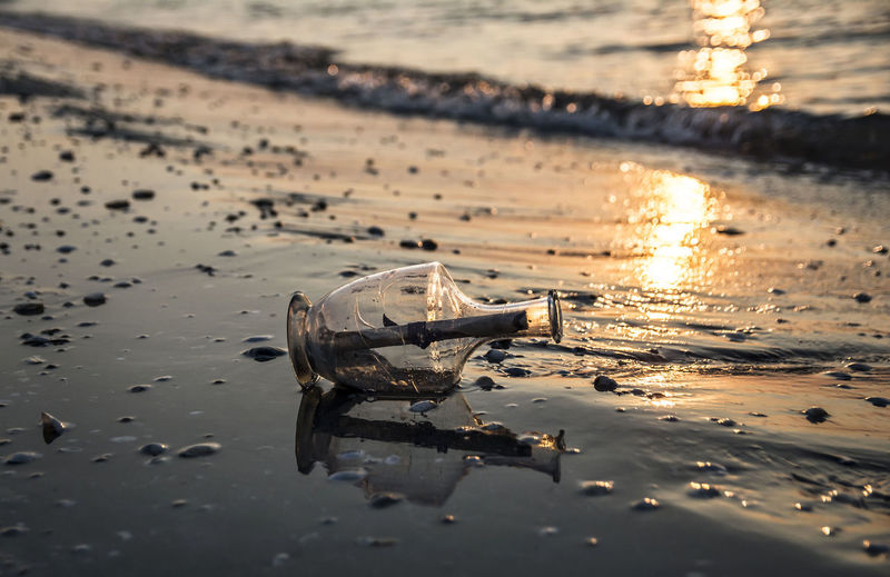 Bottle at beach during sunset