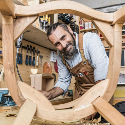 Portrait Of Smiling Carpenter Working In Workshop