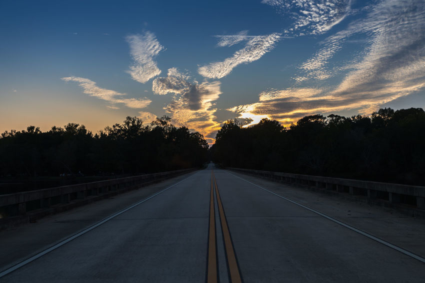 Sunset over a Lonely Road Day Nature No People Outdoors Road Sky Sunset The Way Forward Transportation Tree