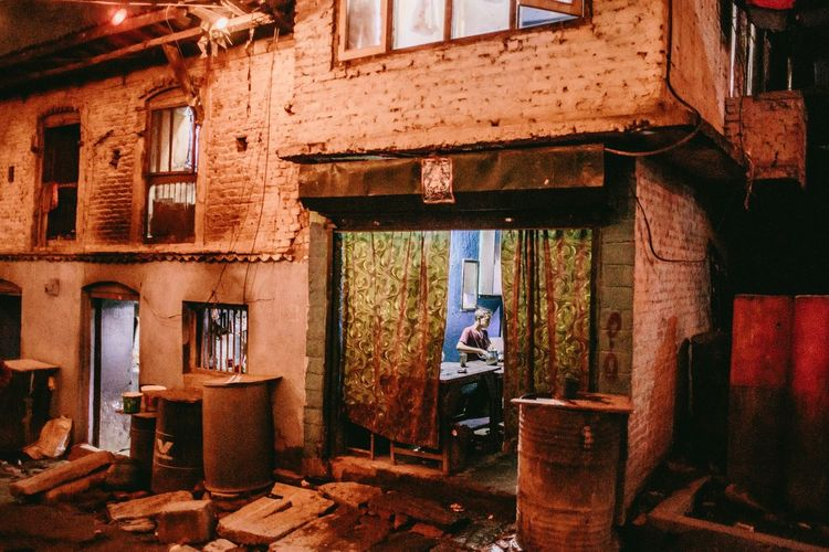 Man standing by window in abandoned building