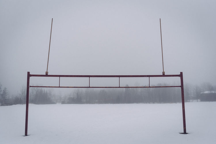Goal post on snowfield against sky