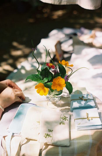 Cropped image of hands by vase on table