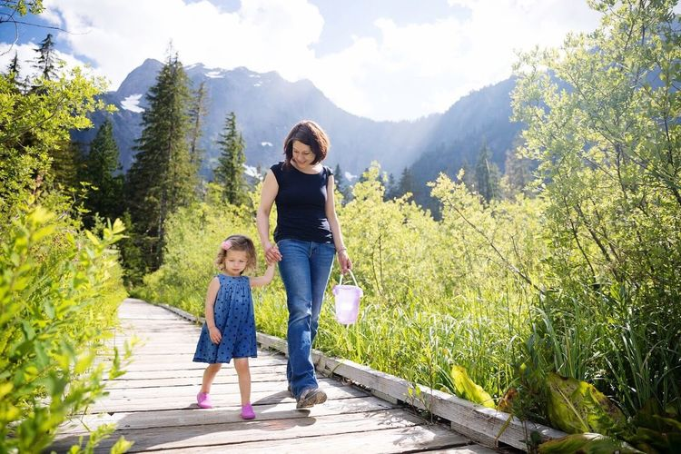 Full length of mother and daughter walking on mountain against sky