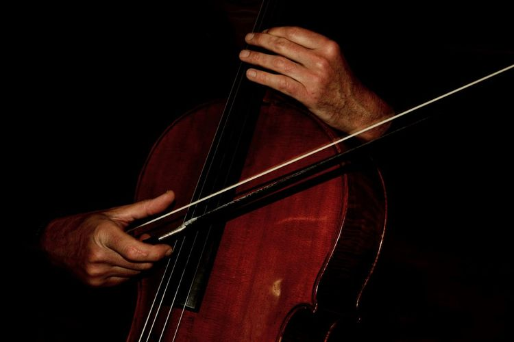 Close-up of man playing cello against black background