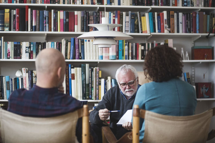 Senior therapist explaining analysis to mature couple against bookshelf at home office